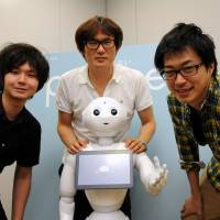 Humor lab (from left): Masato Takahashi, Toshinari Nakano and Kyeong Heon Shin of the new robotics division at entertainment agency Yoshimoto Kogyo pose with pioneering android Pepper. | SATOKO KAWASAKI