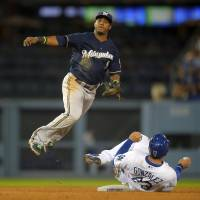Give me a pair: Brewers shortstop Jean Segura tries to turn a double play after Adrian Gonzalez (right) is forced out at second base on Friday. | AP