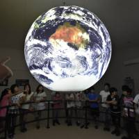 Local elementary school students look at the Science On a Sphere displaying planetary data at the Discovery Center in Higashimatsushima, Miyagi Prefecture, on July 26.  | KYODO
