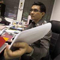 Police Col. Decha Promsuwan, an investigator in a surrogacy scandal involving a Japanese businessman, shows documents on Aug. 26 during an interview at Lumpini police station in Bangkok,Thailand.    AP
