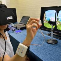 A journalist tries out a new device that uses tactile feedback 3-D technology at a press preview in Tsukuba, Ibaraki Prefecture, on Monday. | AFP-JIJI