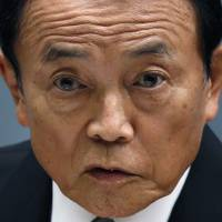 Deputy Prime Minister and Finance Minister Taro Aso holds a news conference at the prime minister's office on Wednesday. | REUTERS