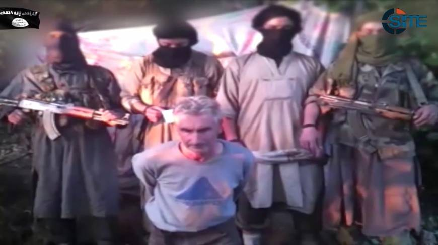 In this still image from video published on the Internet on Wednesday by a group calling itself Jund al-Khilafah, or Soldiers of the Caliphate, members of the group stand behind French mountaineer Herve Gourdel just before beheading him. In the video, the men pledge their allegiance to the leader of the Islamic State group, Abu Bakr al-Baghdadi, before killing Gourdel, 55, who they abducted on Sunday