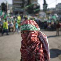 A masked Palestinian boy takes part in a rally celebrating what organizers say was a victory by Palestinians in Gaza over Israel following a ceasefire, in the West Bank city of Ramallah on Saturday. | REUTERS
