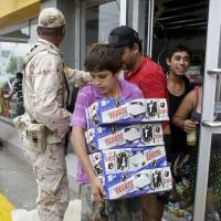 Looting erupts after hurricane thrashes Mexico resorts
