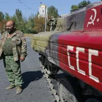 An armed pro-Russian separatist stands next to an armored personnel carrier painted with the hammer and sickle of the former Soviet Union in the eastern Ukrainian city of Donetsk on Tuesday. | REUTERS