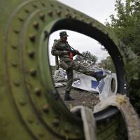 As inquiry is released, Malaysia plane's wreckage still litters Ukraine's east
