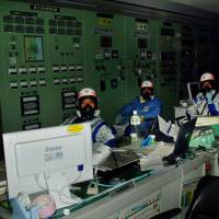 In this photo provided by a Tokyo Electric Power Co. employee, workers await instructions in the control room for reactors 1 and 2 at Fukushima No. 1 power plant on March 12, 2011, right after an explosion ripped through the building housing the No. 1 reactor. | KYODO