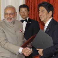 photo cIndian Prime Minister Narendra Modi shakes hands with Prime Minister Shinzo Abe during a signing ceremony at the Akasaka State Guest House in Tokyo on Monday. | POOL