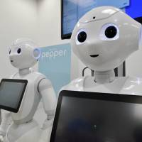 SoftBank Corp.'s humanoid robot Pepper is displayed at a high-tech gadget exhibition in Tokyo in June. Food giant Nestle said on Wednesday its Japan unit plans to put 1,000 of the robots to work as sales clerks at stores across the country. | AFP-JIJI
