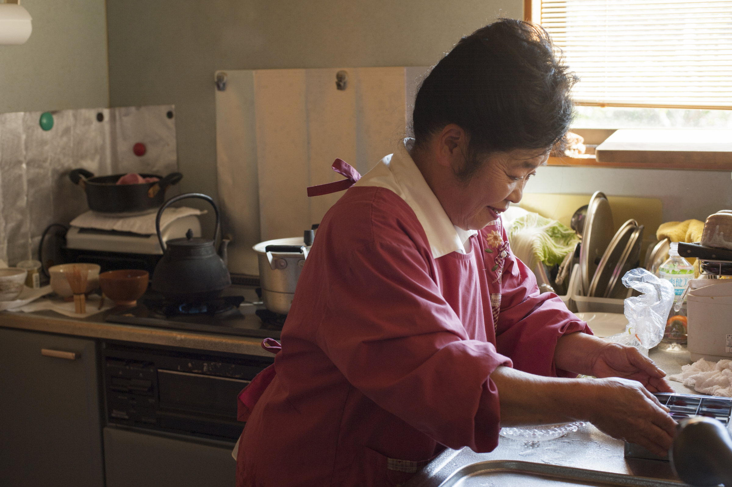 Toshiko Nakamura washes dishes in her kitchen in Keishi, Ooka village, Nagano Prefecture.