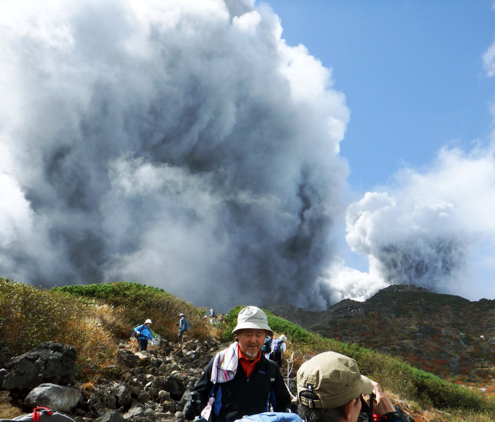 Hikers make their way down Mount Ontake as the volcano erupts on Sept. 27.