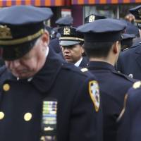 Mayor eulogizes slain officer as cops outside turn backs