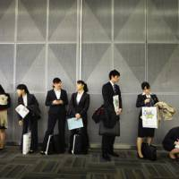 All educated and nowhere to go: Graduates wait in line before attending a company's briefing session as they look for a job in Tokyo on Jan. 22.   AP PHOTO