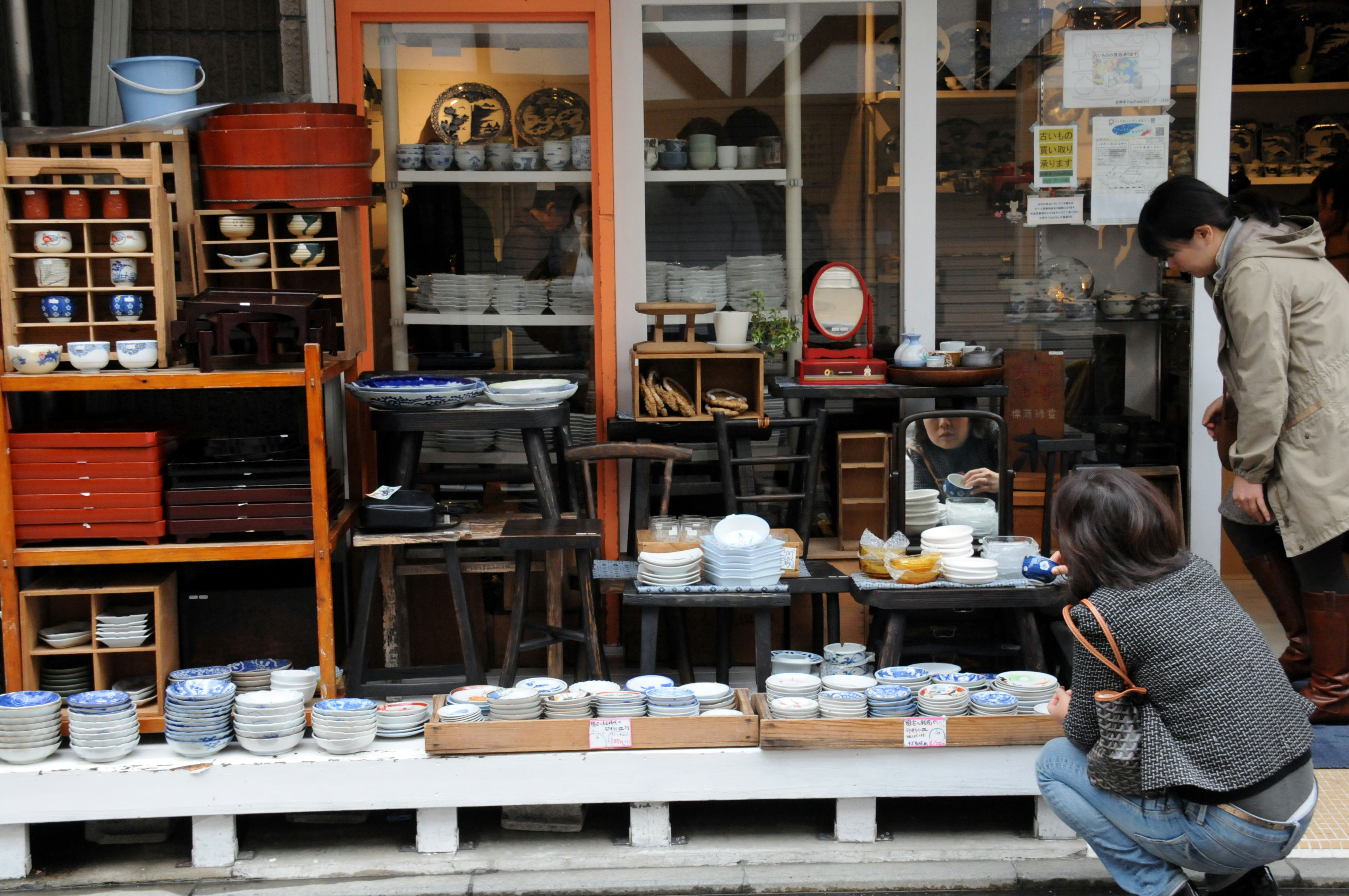 Shoppers browse cups and plates at one of several stores selling antiques in the Kichijoji area.