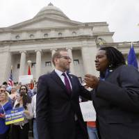 Arkansas governor, like Indiana counterpart, also urges changes to state's religious objection bill