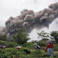 Volatile Indonesia volcano set to blow but thousands of villagers refuse to flee