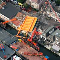 Cranes on river fall on houses, shops in Netherlands; man rescued