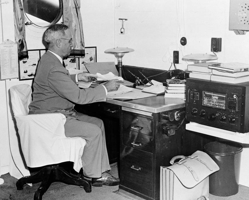 U.S. President Harry Truman, with a radio at hand, reads reports of the first atomic bomb raid on Japan aboard the cruiser Augusta on Aug. 6, 1945, while en route home from the Potsdam conference.