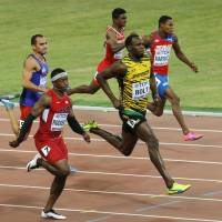 Bolt wins heat in 9.96 seconds, advances to 100-meter semifinals