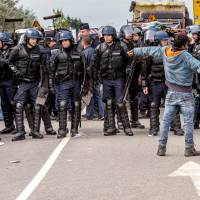 Police officers and gendarmes stand guard during the eviction of around 200 Syrian refugees from a camp site in Calais, northern France, on Monday. | AFP-JIJI