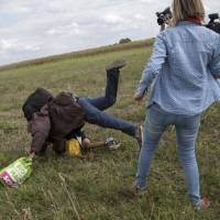 Tired of waiting, refugees breach Hungary border police blockade, take to fields, tracks