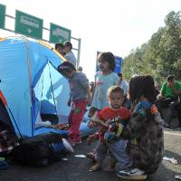 Hungary's sealed border puts squeeze on Serbia; Merkel demands refugee summit