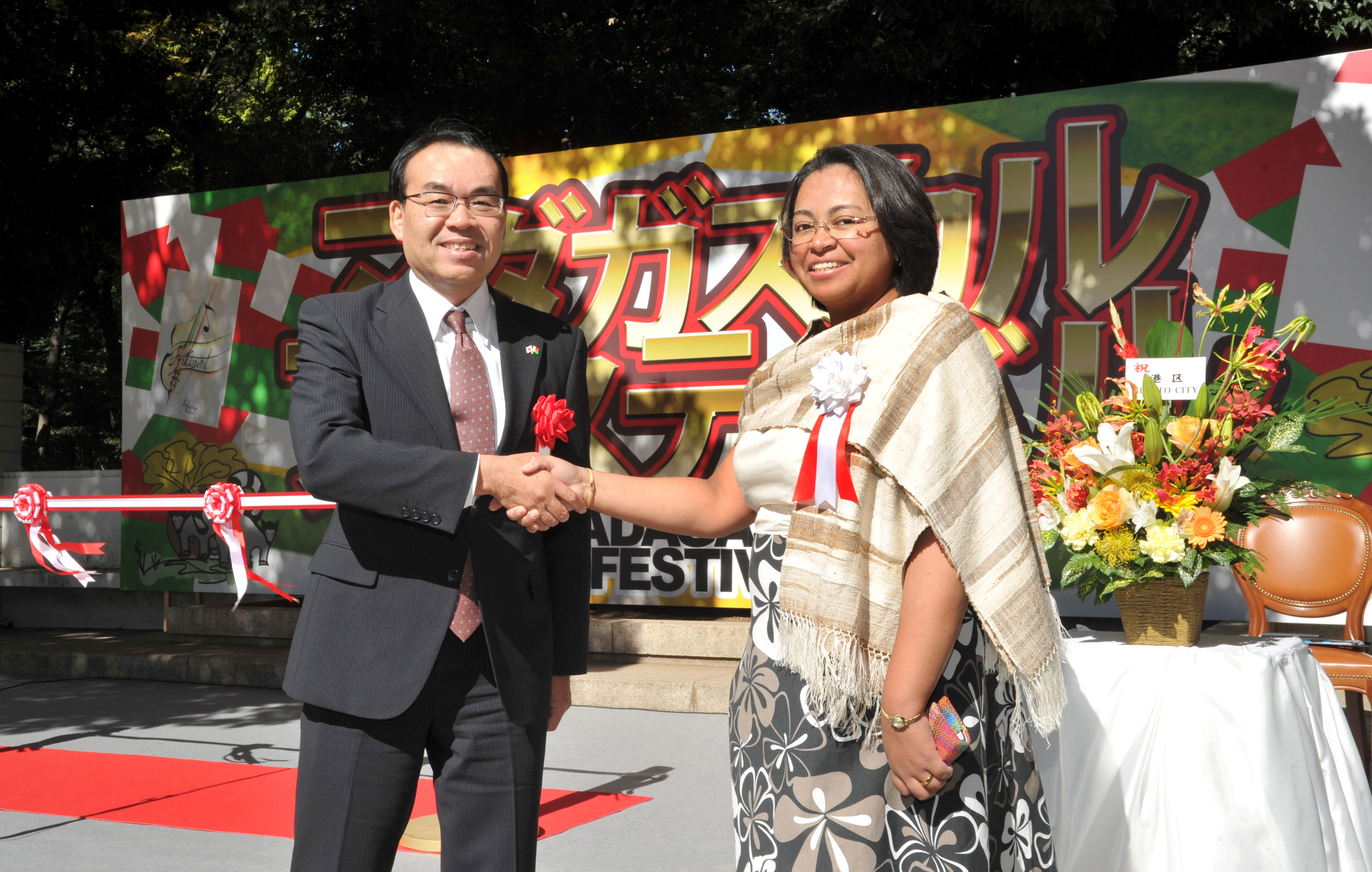 Charge d'Affairs a.i. of Madagascar Rosette Rasoamanarivo (right), shakes hands with Akira Oyaizu, deputy mayor of Minato Ward, Tokyo, during the opening ceremony of the 2015 Madagascar Festival at Arisugawa Memorial Park in Tokyo on Oct. 25. | YOSHIAKI MIURA