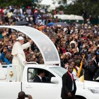 Pope draws rain-soaked throngs for first Africa Mass, warns of 'grave environmental crisis'