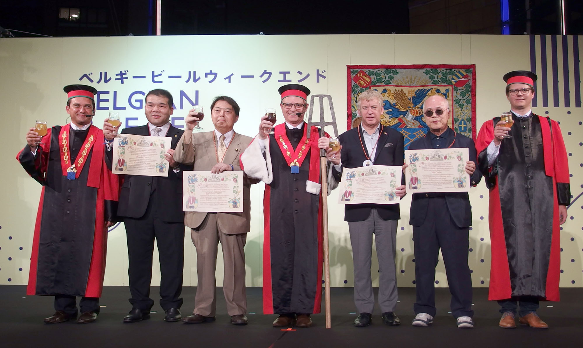 "The four new members of the Knighthood of the Brewers' Mashstaff (from left, holding certificates) former ozeki Tochiazuma; former agriculture minister, and President of the Japan-Begium Parliamentary Friendship League Yoshimasa Hayashi; Belgium's Ambassador to Japan Gunther Sleeuwagen; and Writer Go Osaka pose with members of the knighthood during a ceremony at ""Belgian Beer Weekend 2016,"" which runs through Sept. 25, at Roppongi Hills Arena in Tokyo on Sept. 16. 