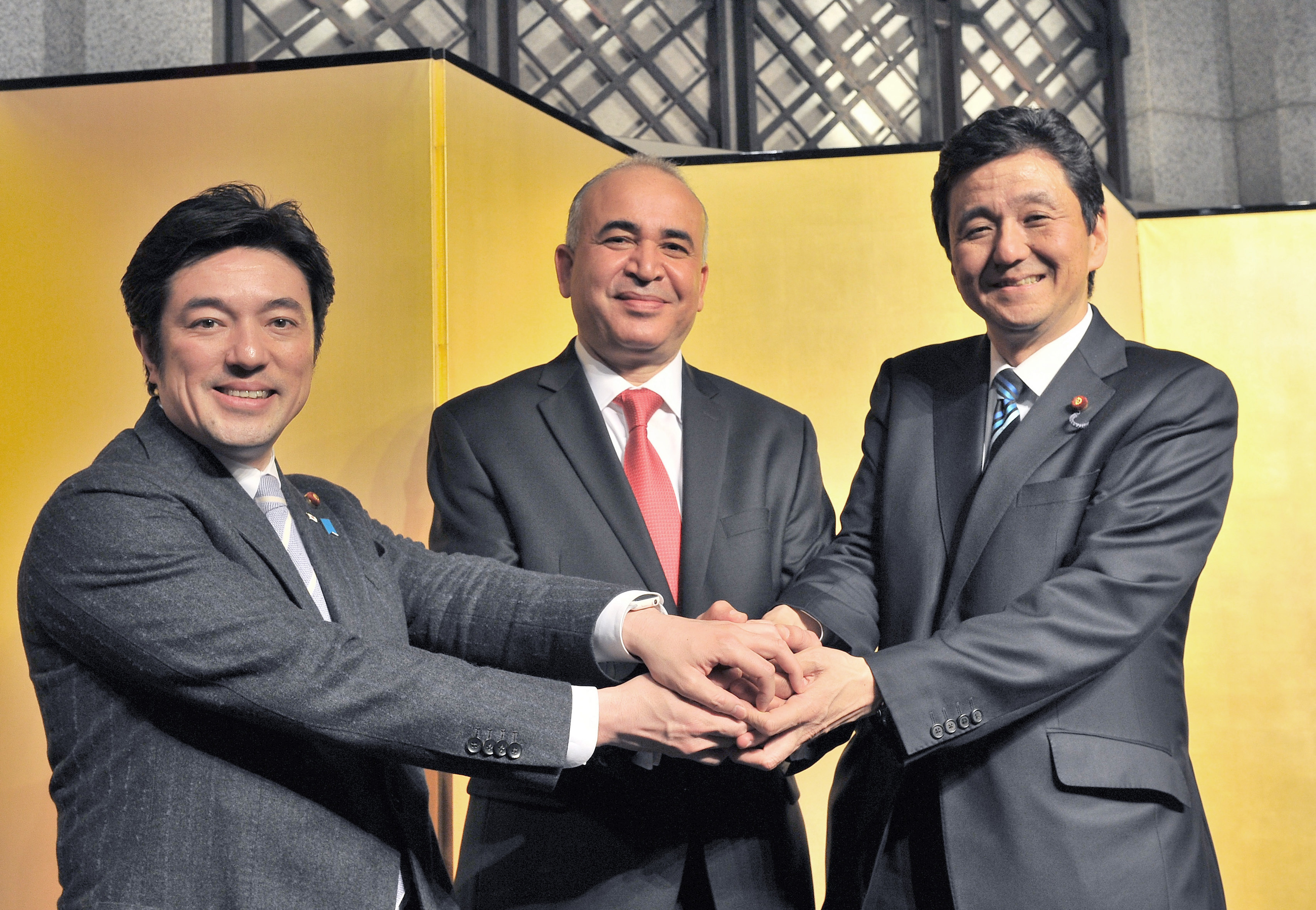 Tunisia's Ambassador Kais Darragi (center) joins hands with Japan Tunisia Parliamentary Committee Secretary-General Yasuhide Yamanaka  and Chairman of the committee and State Minister for Foreign Affairs Nobuo Kishi at a reception to celebrate the country's 61st independence anniversary at the Hotel Okura, Tokyo, on      March 24. yoshiaki miura |