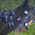 Grim discovery: Investigators gather at a crime scene in Kure, Hiroshima Prefecture, after the body of a 16-year-old girl was discovered.