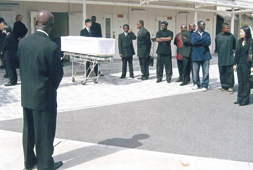 Final journey: The casket is wheeled out of the viewing room after the funeral service for Gilbert.