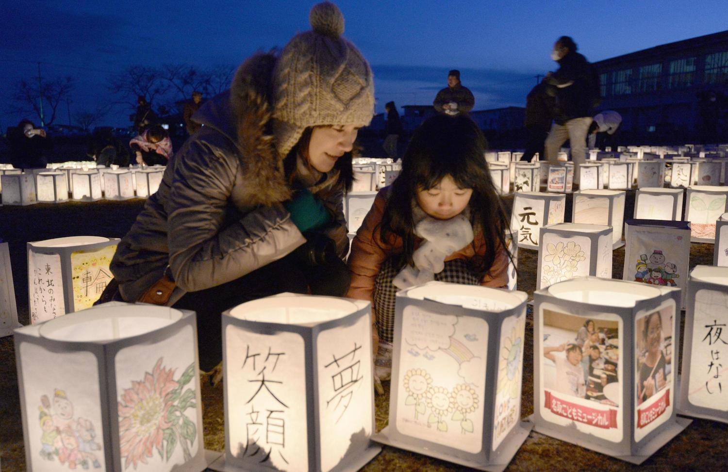 A mother and her daughter attend a candle-lighting event held Sunday to commemorate the third anniversary of the March 11 tsunami and earthquake in Natori, Miyagi Prefecture, one of the worst-hit areas.