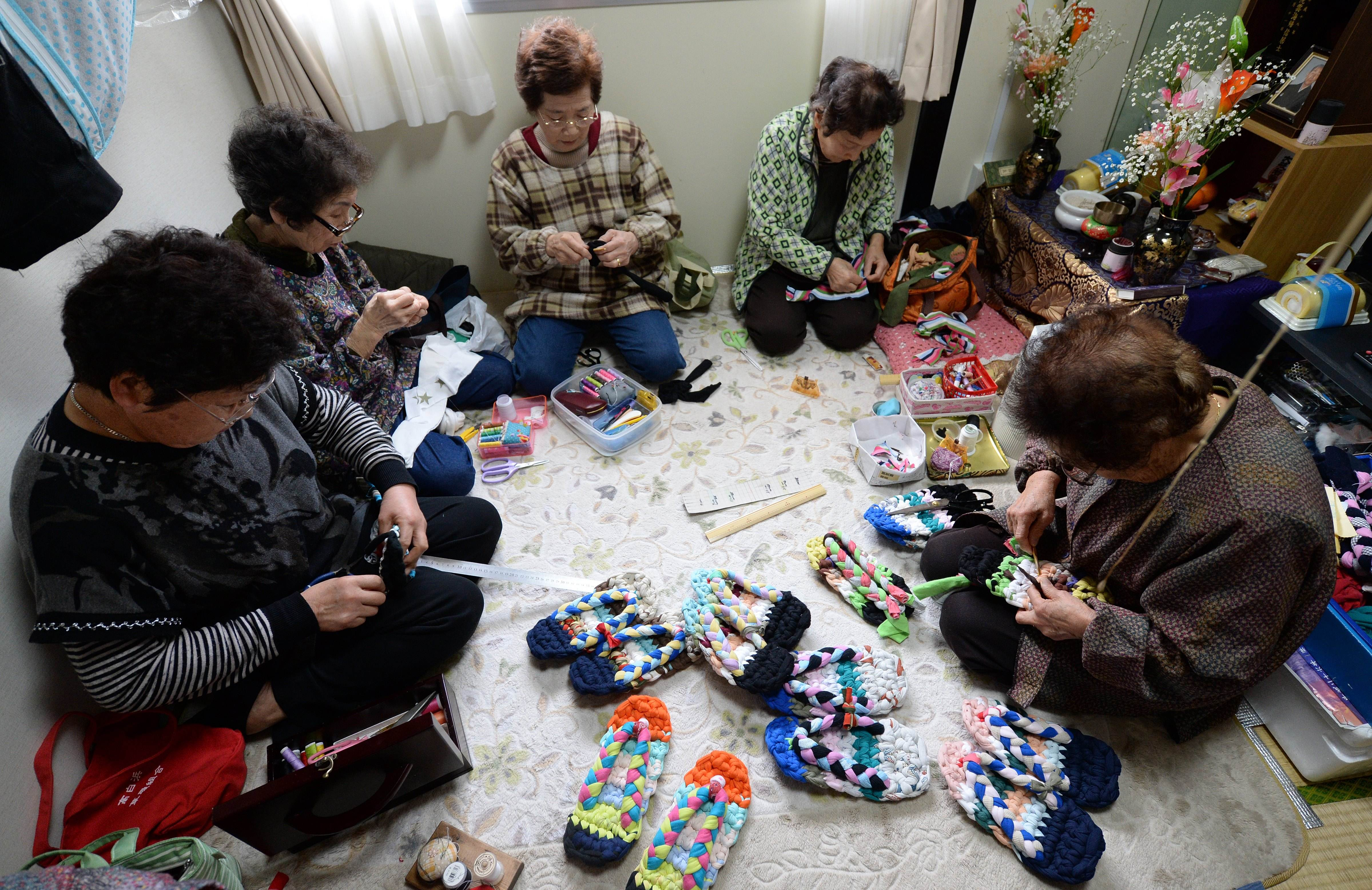 Elderly women making sandals from used T-shirts in a small room of a temporary housing complex in Ishinomaki, Miyagi Prefecture, on March 3, 2014.