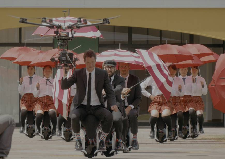 With the drone flying overhead, OK Go with school girls in tow, glide through the stadium courtyard.