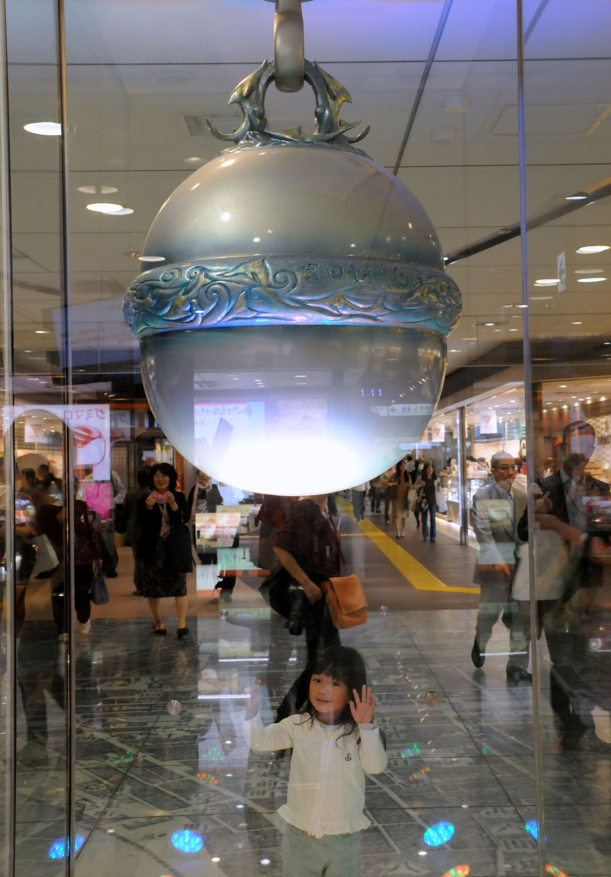A child looks at a large, glass-covered silver bell that has become a popular meeting spot in JR Tokyo Station.
