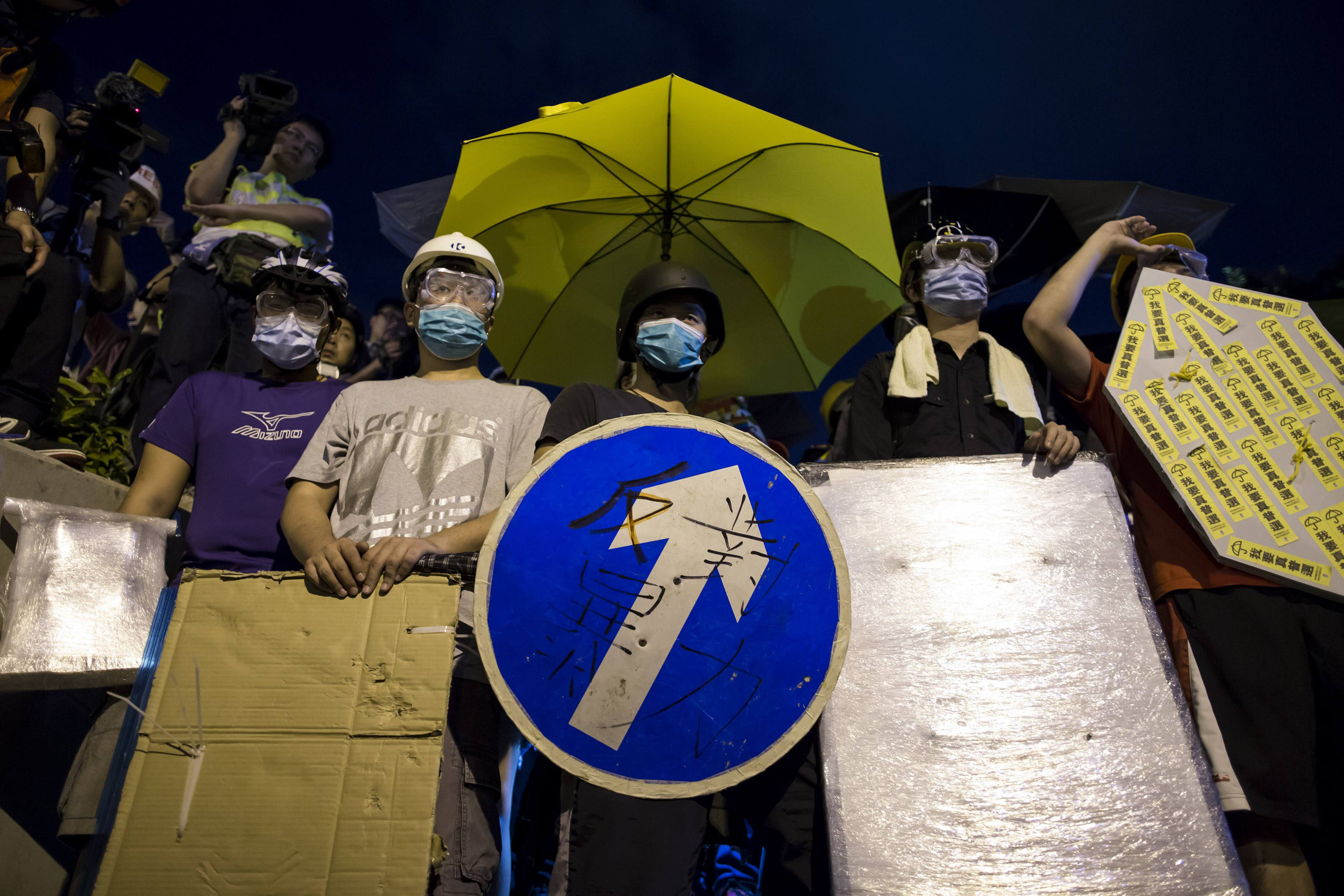 A pro-democracy protester holds a road sign as a shield while standing in front of riot police close to the chief executive's office in Hong Kong on Nov. 30.