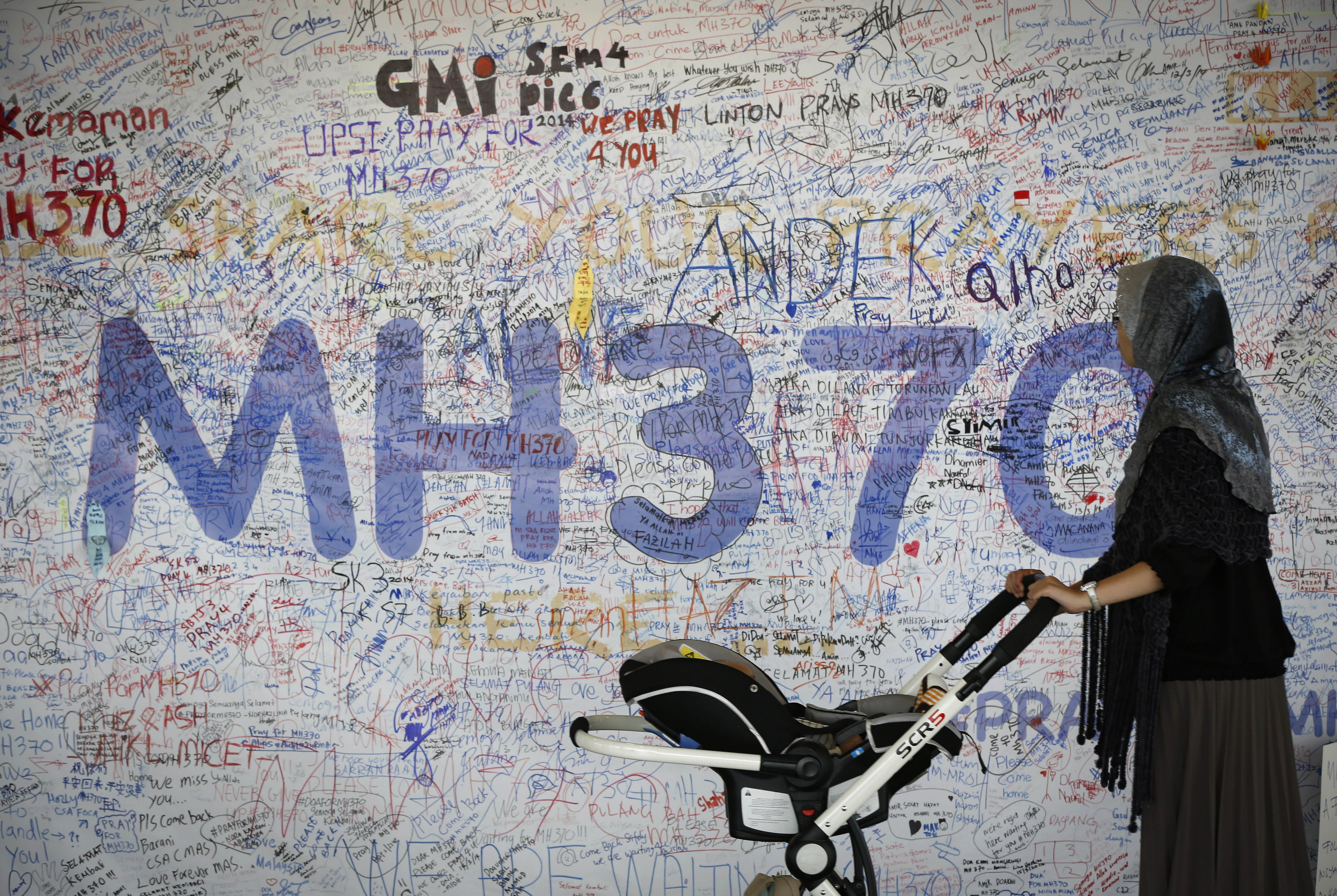 A woman walks past a board displaying messages of hope for passengers aboard missing Malaysia Airlines Flight MH370 at Kuala Lumpur International Airport on March 19.