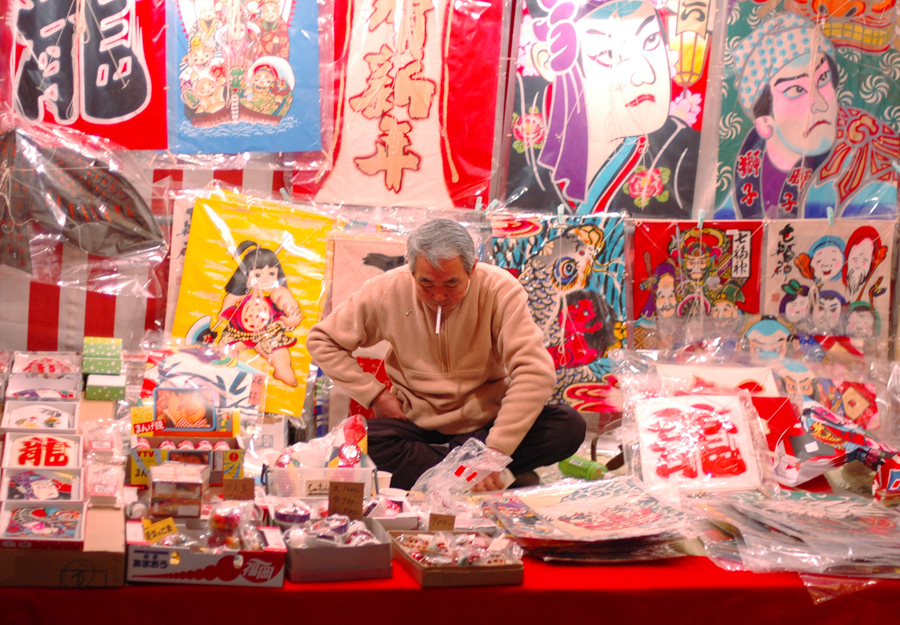 A worker is surrounded by many decorative kites.