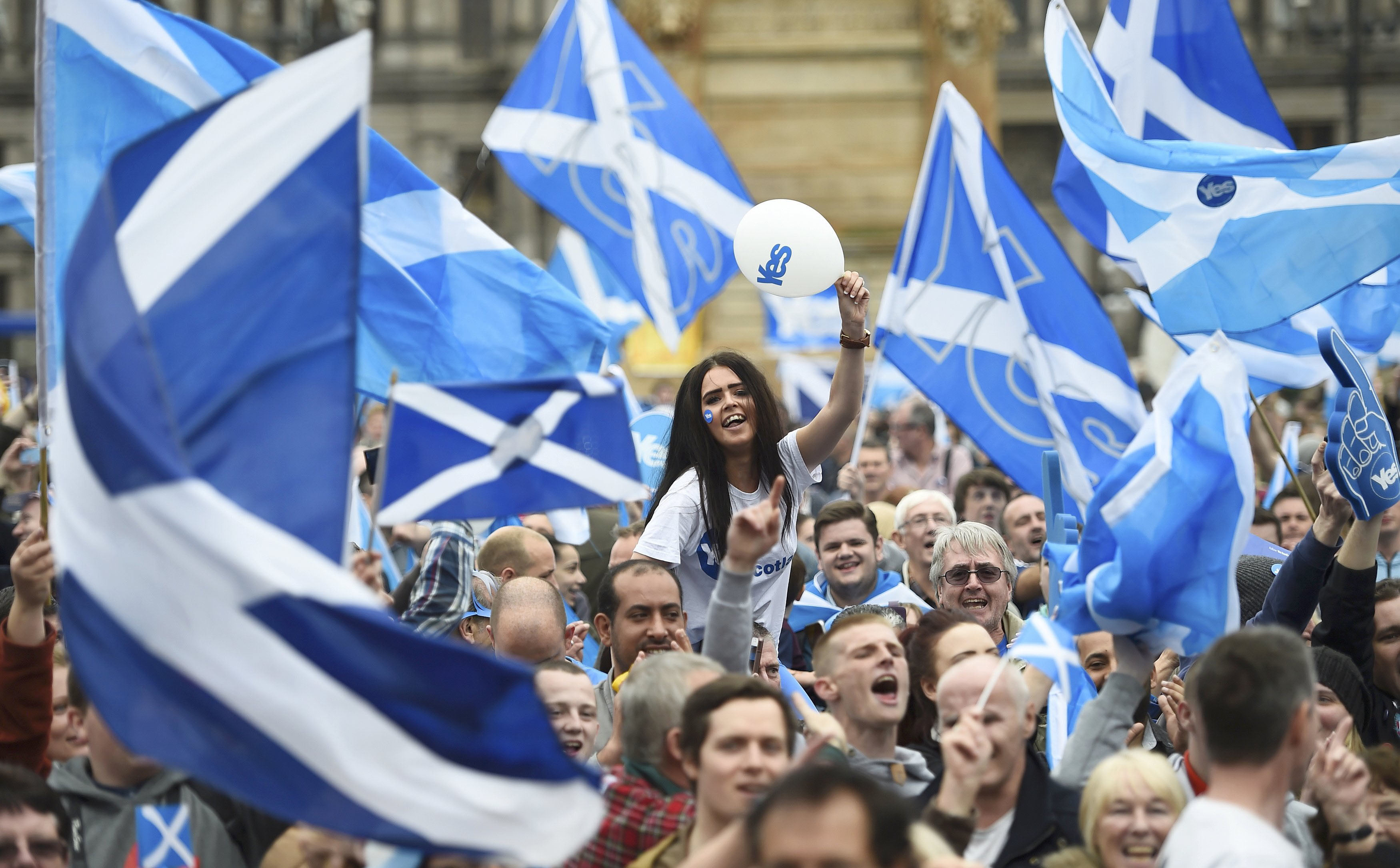 Scottish pro-independence campaigners wave Saltire flags at a