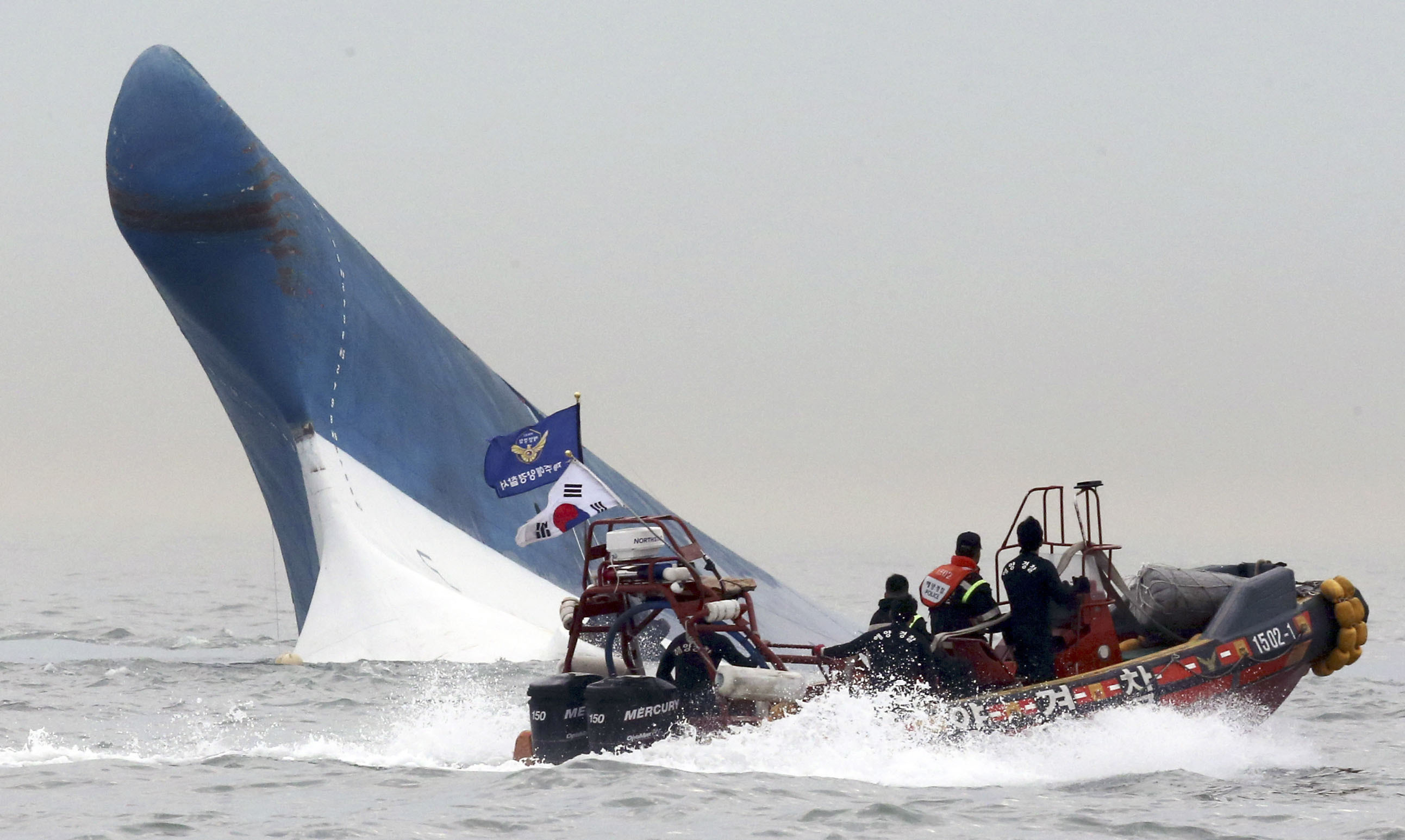 South Korean Coast Guard officers attempt to rescue passengers from the sinking Sewol ferry on April 16 after the overloaded vessel capsized near Jindo Island, off the southwest coast.