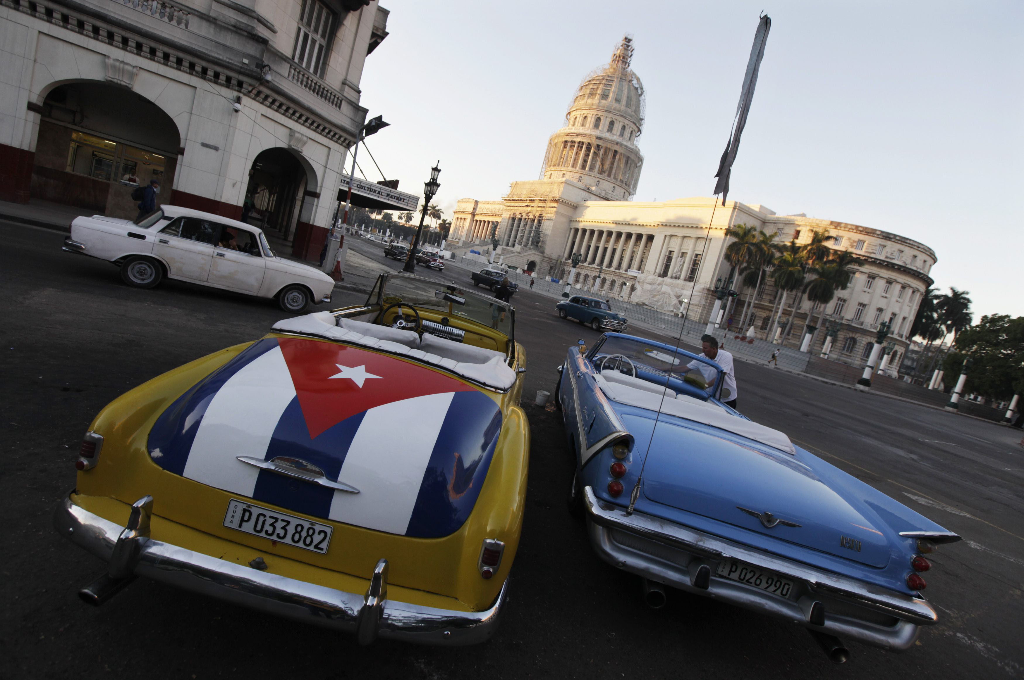 A vintage American car painted with a Cuban flag is parked near the Cuban Capitol in Havana on Dec. 18.