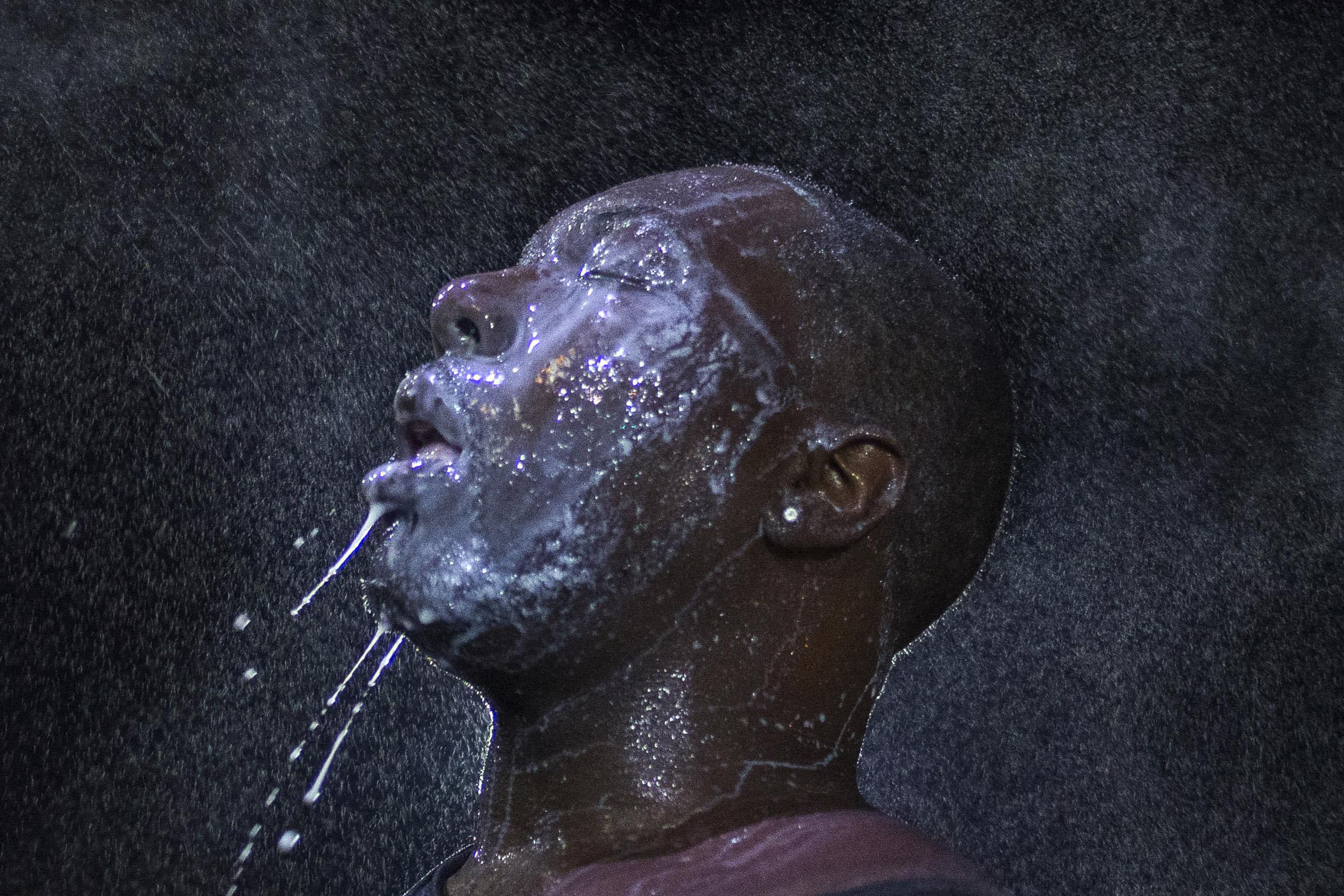 A man is doused with milk and sprayed with mist after his eyes were affected by a chemical irritant used by police attempting to control riots in Ferguson, Missouri, on Aug. 20.