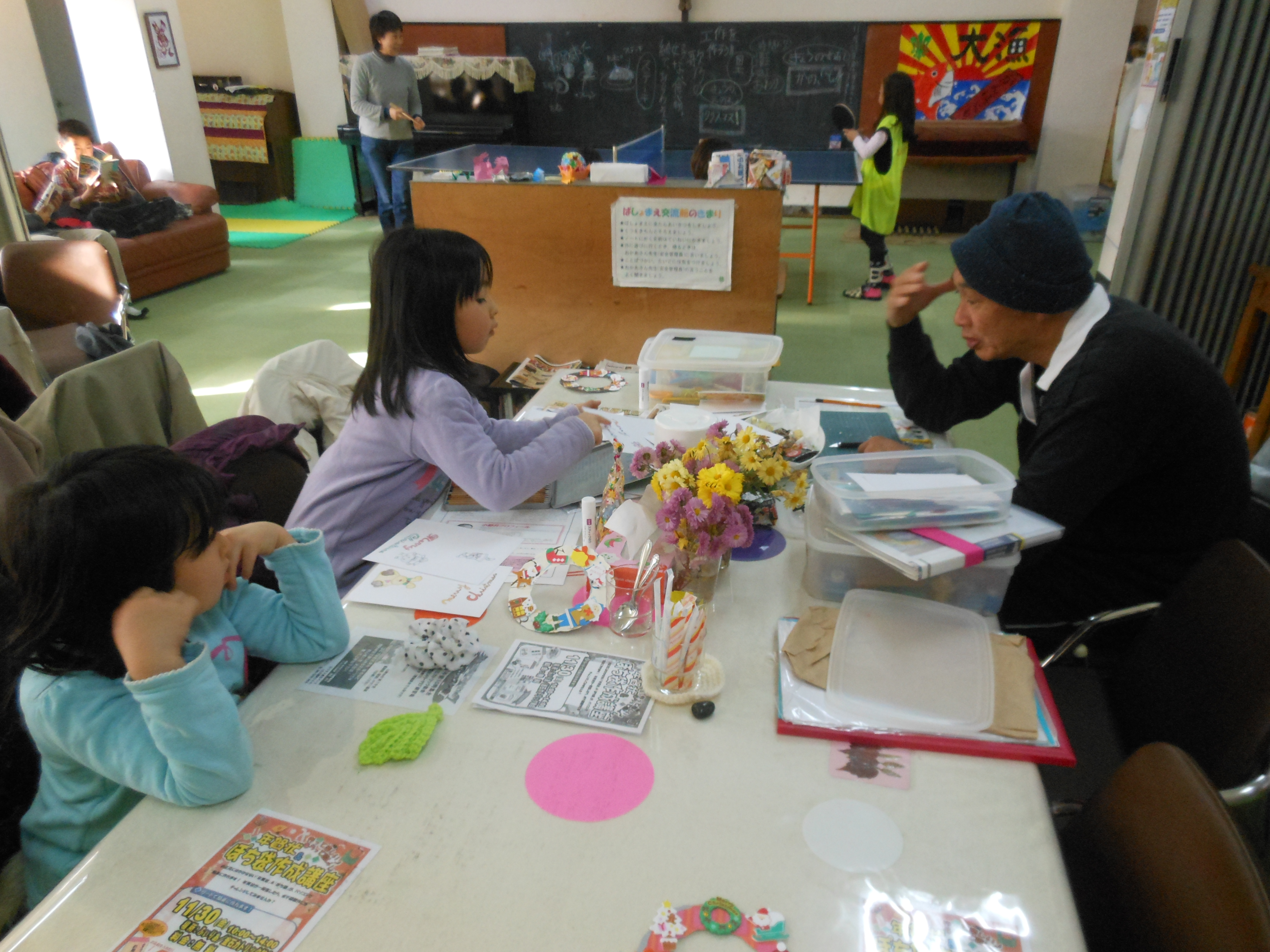 Community leader Katsumi Sawaguchi (right) talks with children at the Philia Cafe run by the Catholic charity Caritas Japan in Kamaishi, Iwate Prefecture.