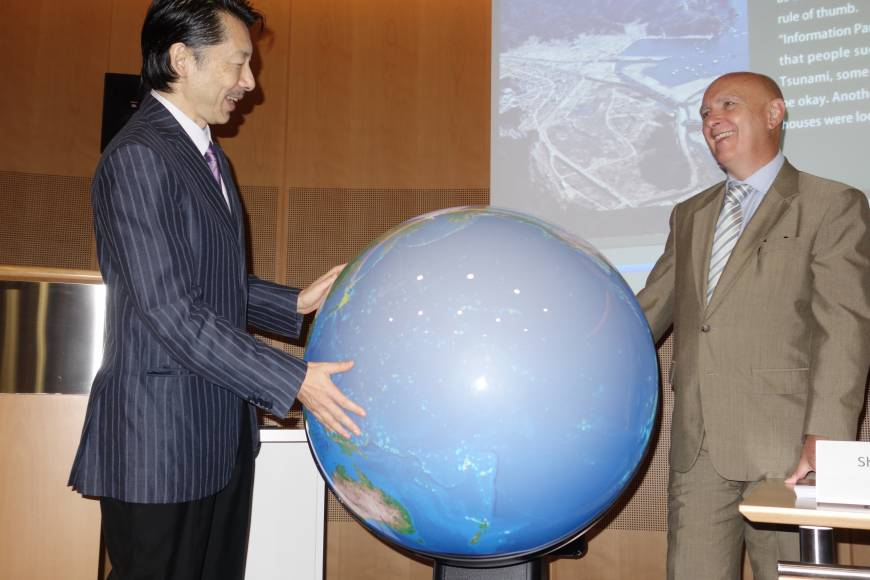 Professor Shinichi Takemura demonstrates his Tangible Earth, an interactive globe, with the head of UNISDR