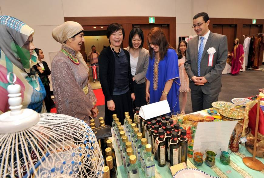 Akie Abe (center), visits the Tunisian booth as Tunisian Ambassador Farhad Khlif (right), and his wife, Mounira (second from right) explain the products.