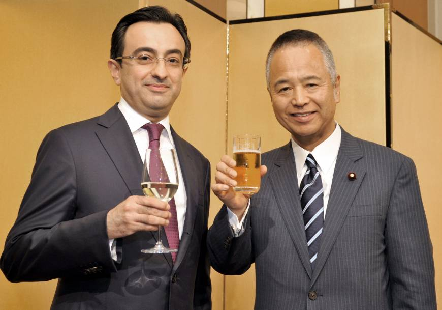 Azerbaijan Ambassador Gursel Ismayilzada (left) welcomes, Akira Amari, chairman of the Japan-Azerbaijan Parliamentary Friendship League, minister in charge of economic revitalization and state minister for economic and fiscal policy, during a reception to celebrate the country