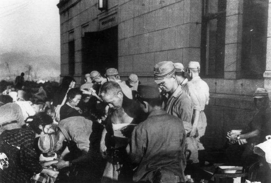 Atomic bomb survivors receive emergency treatment by military medics on Aug. 6, 1945, in Hiroshima.