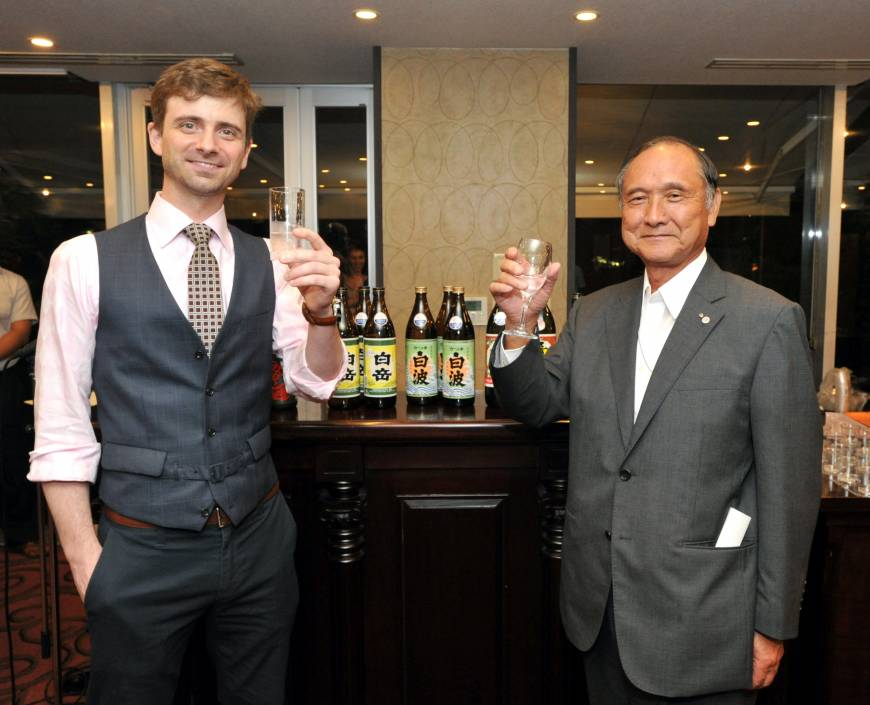 Shochu (distilled spirits) sommelier Christopher Pellegrini (left) and Shigeyuki Shinohara, chairman of the Japan Sake and Shochu Markers Association, raise their glasses to promote